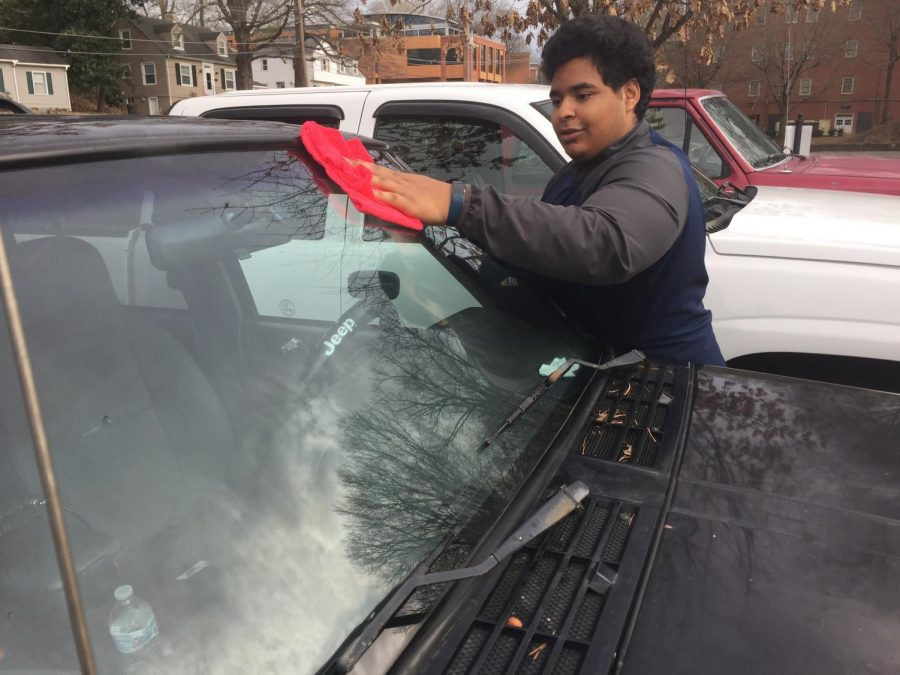 Sophomore Ricardo Roman-Flores uses a towel to clean his windshield.