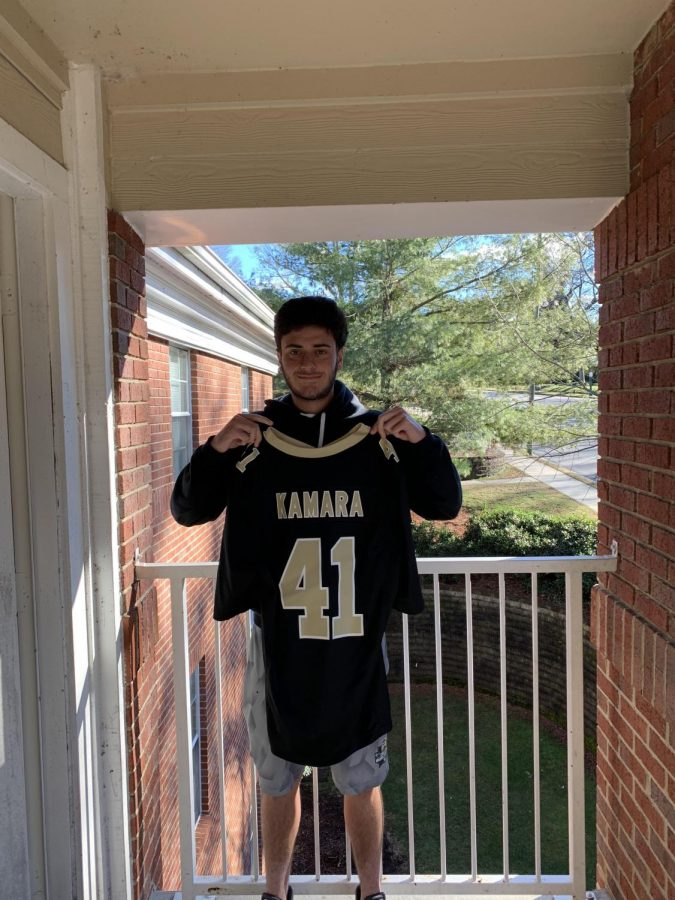 Junior Trevor Ramagos is holding his favorite sports jersey from his hometown.