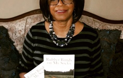 Dr. Annie  Wimbish holds two copies of her autobiography, Rubber Bands on My Socks.