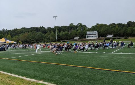 Students sit, socially distanced, on Daly Field for the pinning ceremony.
